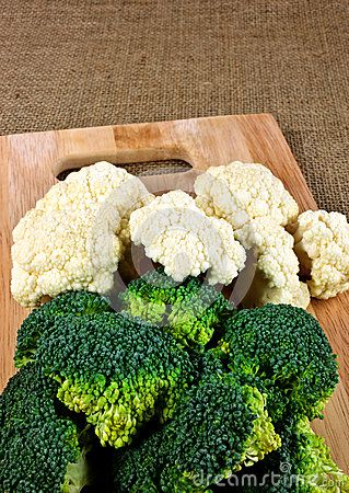 Broccoli and cauliflower pieces on a wooden cutting board.