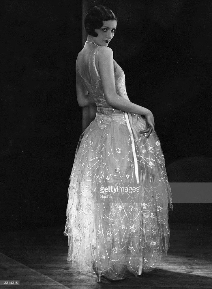 A model wearing a Norman Hartnell evening gown.