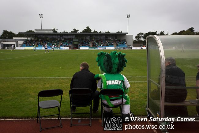 Guernsey 0 Corinthian-Casuals 1, 10/09/2017. Footes Lane, Isthmian League Division One. Mascot Roary the Lion sitting on the home bench next to the club's manager as Guernsey (in green) take on Corinthian-Casuals in a Isthmian League Division One South match at Footes Lane.