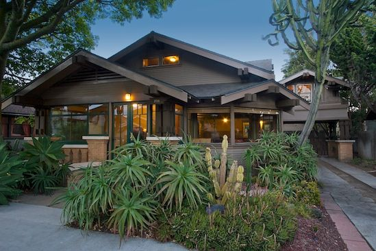 Cali Bungalow. Love the earth tone paint & trim, the glow from interestingly-shaped windows, the welcoming porch, and the lovely plants.