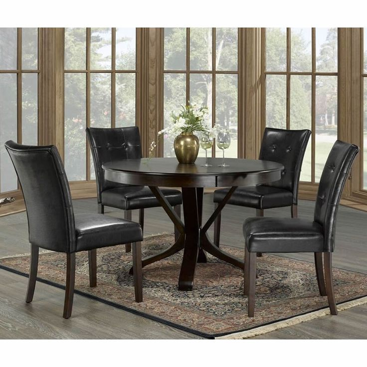The #Dakota #dining set is made with wooden frames featuring an espresso finish. While the table features a pedestal base, the side chairs feature flared legs, black leatherette seat and backrest with button tufting. This set includes a dining table and 4 side chairs. #home #dinner #table