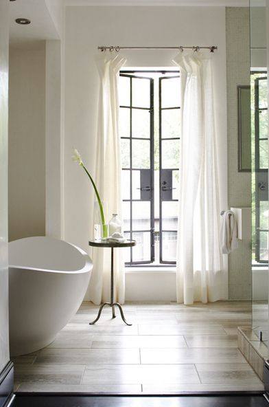 Gorgeous, serene bathroom design with freestanding tub, French brass accent table and white drapes. Jeff Herr Photography