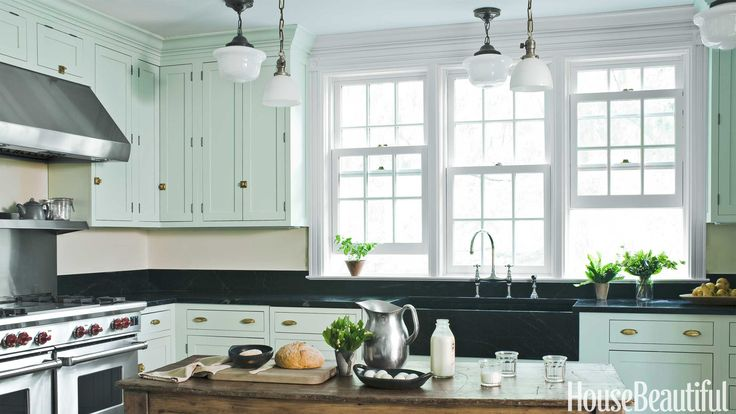 For a new kitchen in Mount Kisco, New York, Shaker-style cabinets by Plain & Fancy, painted Teresa's Green by Farrow & Ball, have a wonderfully old-fashioned but surprisingly fresh look. Vintage pendants hung at different heights provide ambient and task lighting. The dark brass schoolhouse lights were found at Scherer's Architectural Antiques. John M. Hall  - HouseBeautiful.com