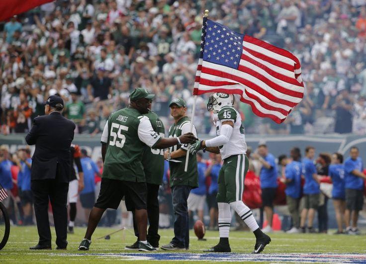 Jets #45 Rontez Miles hands the flag to 2001 Jet Marvin Jones as the New York Jets host the Cincinnati Bengals in NFL action. 9/11/16 East Rutherford, N.J. (John Munson | NJ Advance Media for NJ.com)