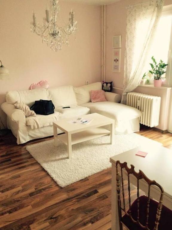 Helles Wohnzimmer mit weißer Couch und Teppich und rosa ...