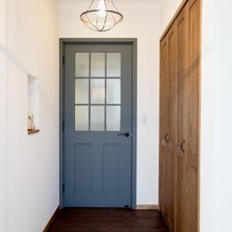 ビンテージ感溢れるスキップフロアの家 (北欧カラーの建具がポイントの玄関)