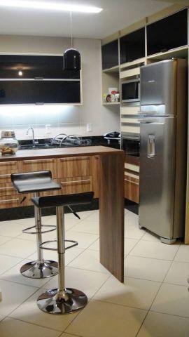 Em um apartamento localizado em Jaraguá do Sul (SC), a cozinha integrada às salas de jantar e de TV tem 7,5 m². Os móveis são de MDF com estrutura em cor bege, padrão amadeirado nos armários inferiores e portas basculantes feitas de vidro preto. Projeto da arquiteta Elis Ferraresi Freiberger.
