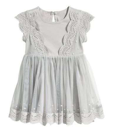 Light gray. Dress in soft lace with cap sleeves, gathered seam at waist, and opening at back of neck with button. Jersey lining.