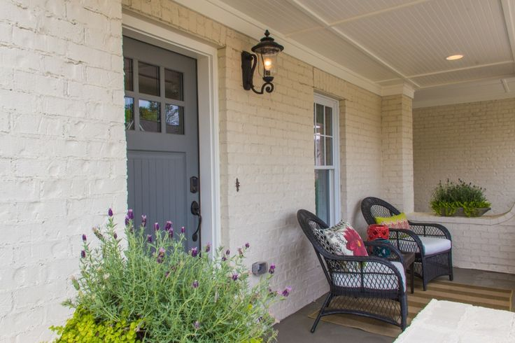 Craftsman Front Door with Painted brick wall, Outdoor wicker furniture, Covered front porch, exterior stone floors