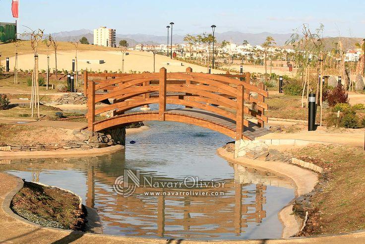 Puente de madera curvo ubicado en jardines de la urbanización Mar de Pulpí by navarrolivier.com