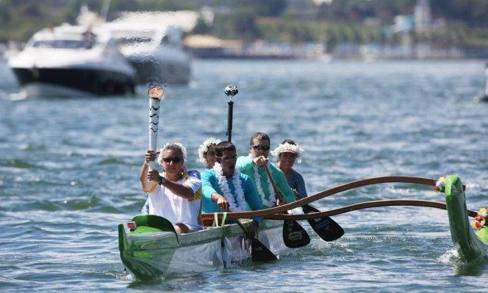 Participantes do revezamento levam a tocha em uma Canoa Havaiana, no Lago Paranoá Michel filho / Agência O Globo