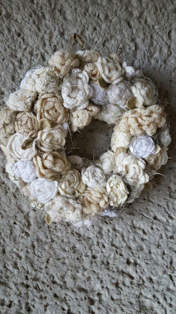 Eigen ontwerp van een rozenkrans in verschillende tinten wit. Met een beetje tirlantia en gehaakte licht groene blaadjes op ijzerdraad. Ik heb hiervoor vooral restjes garen gebruikt. Ook eigen gesponnen wol. Maar vooral veel katoen.
