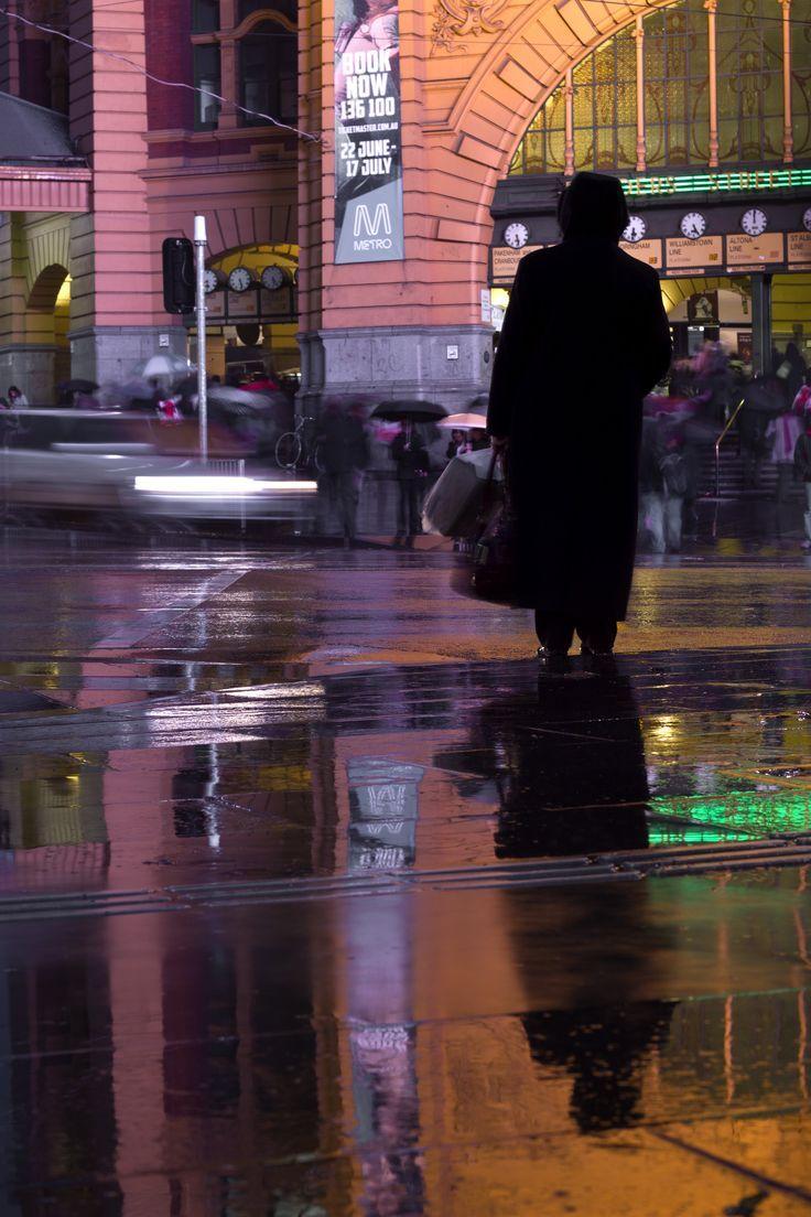 Rainy night reflection outside Flinders Street Station in Melbourne, Australia