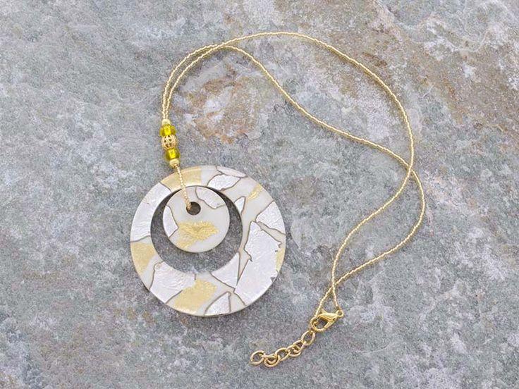 Pendente in vetro di Murano con doppia corona a forma di cerchio.  La base è di colore bianco con inserti in foglia d'argento e foglia d'oro.  La catena è fatta di perline in conteria, tutto in materiale anallergico (NICKE FREE). Il cerchio è il simbolo dello spirito e dell'immaterialità dell'anima.