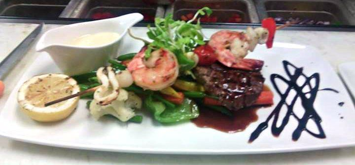 Seafood Skewer and Beef Tenderloin, topped with red wine jus and a side of lemon cream sauce