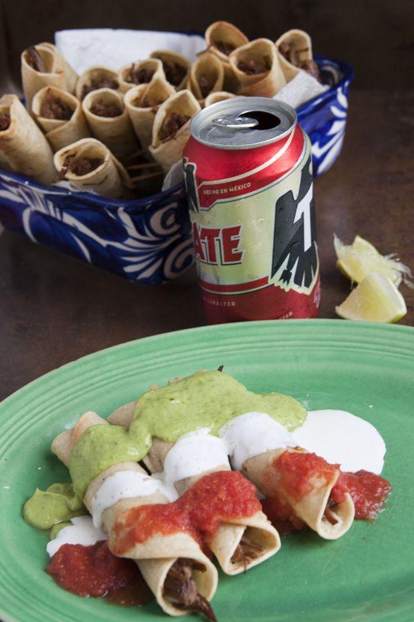 Brisket Flautas Banderas topped with an avocado and tomatillo salsa, crema Mexicana, and a warm tomato broth.