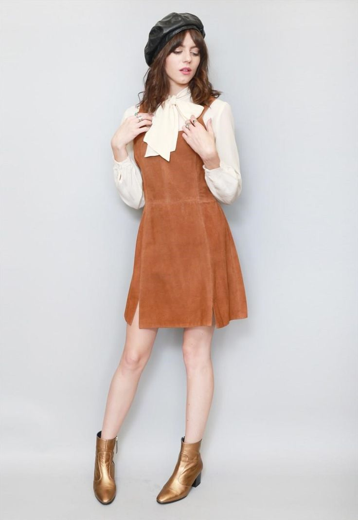 """Vintage 1970s Brown Suede Rifless Mini Dress. Gorgeous brown suede pinafore style mini dress with a zip at the back. Features a soft caramel suede. Two short vents at the hem.  Size UK 12 approx. Our model is a size 8. Please see sizing for measurements. If you love Peekaboo Vintage, """"follow"""" us here on ASOS. First-time buyers will receive a discount code and you will also be kept up-to-date with our daily arrivals. Our hassle-free returns means you can shop with ease. Lots of Love ..."""