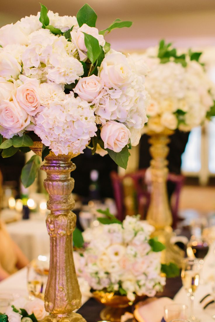 the king table for the wedding party was highlighted by two large arrangements of white hydrangea, white roses, champagne roses, green parrot tulips and lemon leaf on gilded gold pedestals. the gorgeous bridal bouquet rested on a mossed antique brass bowl in front of the bride and groom.