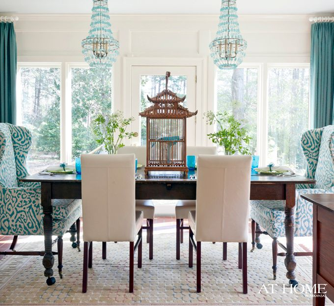 """Yhis inviting home belongs to El Dorado, Arkansas interior designer Andrea Brooks–who admits to being fearless (and obsessed!) with color.The layers of turquoise in her dining room on the window treatments and wingback host chair fabric were all inspired by the pair of gorgeous Arteriors Duke chandeliers!  I also love her front door painted Sherwin Williams """"Blue Peacock""""!"""