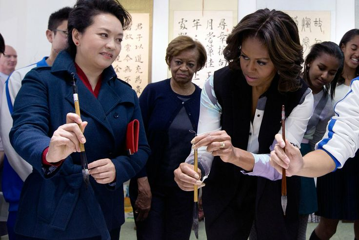 Peng Liyuan, wife of Chinese President Xi Jinping shows U.S. first lady Michelle Obama how to hold a writing brush as they visit a Chinese t...