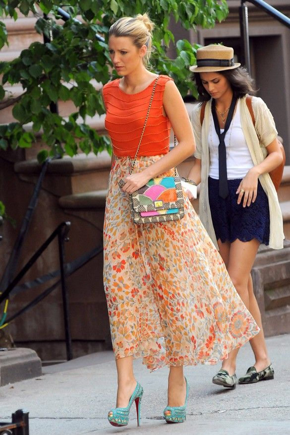 Blake Lively wears an orange top, printed skirt, printed bag, and turquoise heels on the set of Gossip Girl