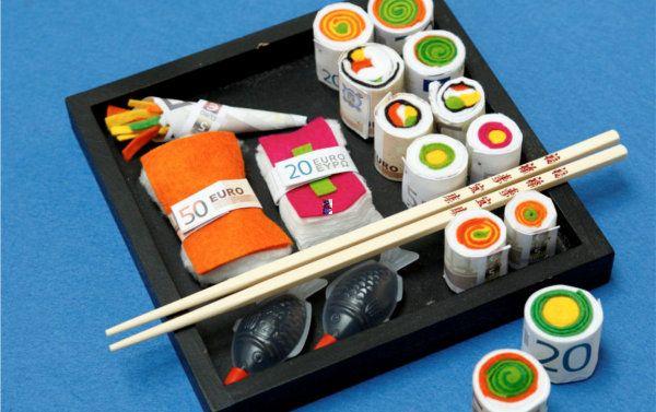 Hier wird der Rubel im wahrsten Sinne gerollt. Mithilfe von buntem Filz und ein paar originalen Accessoires aus dem Asia- Laden verwandeln sich Zehner, Zwanziger oder Fünfziger in appetitliche Sushi-Rollen. Materialien: Filz in verschiedenen Farben Geldscheine Stecknadeln Schere Watte Eine Unterlage für das gebastelte Geld-Sushi, Sushi-Stäbchen und Soja-Soße zur Dekoration So geht das: Makis (gerollte …