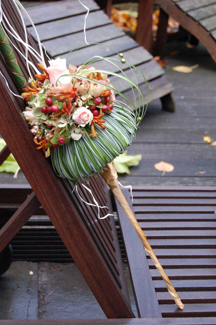 Modern bruidsboeket in herfst tinten, zachtroze, oranje, rood. Rand van berengras en verlengd handvat. www.meesterlijkgroen.nl