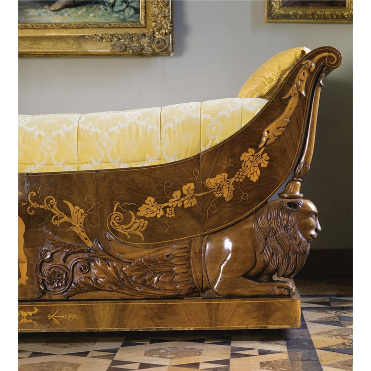 An unusual North Italian carved walnut and fruitwood inlaid lit en bateau circa 1830 with over scroll ends, the front with carved grotesque sea creatures and inlaid with fruiting vine garlands, the centre with a winged figure between carved recumbent lions with acanthus and scrolled decoration, on an inlaid plinth and castors This bed will be sold toghether with a bedspread designed by Versace.