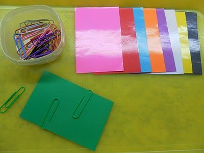 Matching coloured paper clips to coloured card, using fine motor skills to manipulate paper clip onto paper