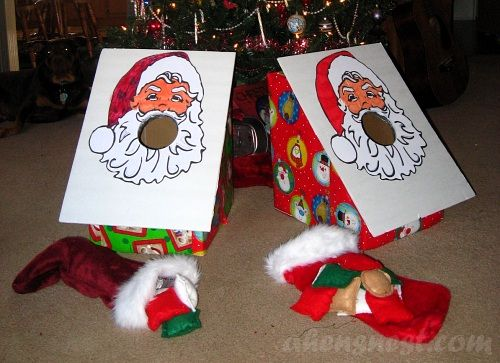 """I like the idea of a bean bag toss game, but I would alter it to have a picture of Santa with his sack.  The sack would have three holes and the kids would toss bean bag """"presents"""" into the holes."""