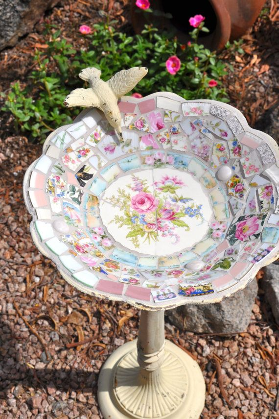 To turn an old birdbath into a pretty backyard piece, cover the bowl in vintage china and pottery using white grout to hold your design together. Featuring rose printed tiles, this one would blend in with blooms in your garden.