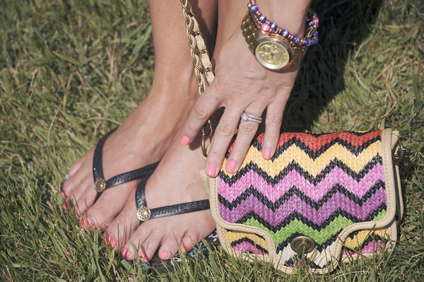 An infield reveler shows of her purse, sandals, and jewelry at Preakness 2012.