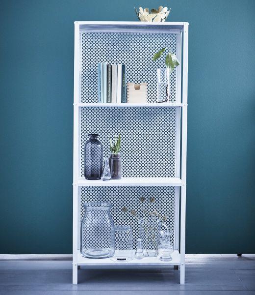 Étagère IKEA HYLLIS blanche décorée de livres, de plantes et de vases en verre.