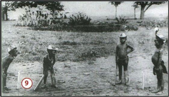 Uitgerust met slaghout, pet en beenbeschermers spelen deze Afrikaanse jongens cricket in een Britse kolonie.