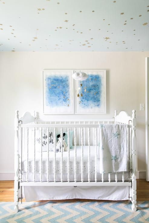 Chic nursery decorated with blue abstract art, white vintage crib dressed in Aden & Anais Night Sky Starburst Classic Crib Sheets. Ceiling painted in Behr Rainwashed matches the Baby Jives Star Cloud Mobile in Gold that hangs above the crib | Designed by Jess for Style Me Pretty