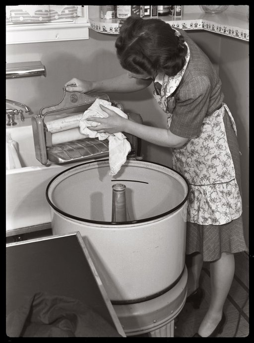 """""""Through the Wringer"""" (1942) • """"To keep your wringer operating properly, dry rolls thoroughly after use with a soft cloth and then release lever which removes pressure from the rolls."""" • by Dave • Photo: Ann Rosener for the Office of Emergency Management"""