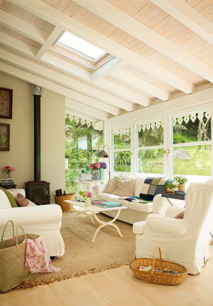 Un salón de cuento  Una decoración muy luminosa en blanco y con la alegría del color en los complementos. Con chimenea de hierro, techo abuh...
