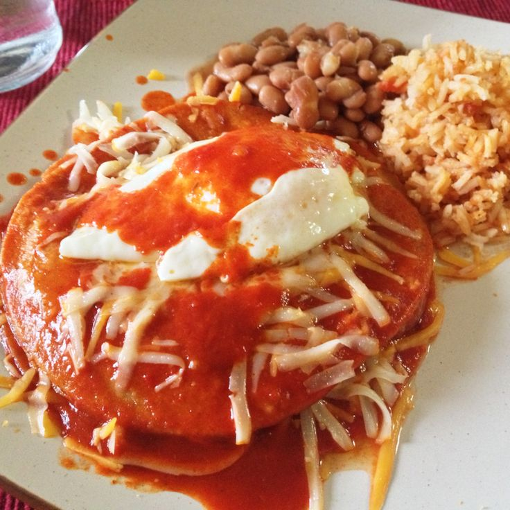 New Mexico & Southern Colorado Stacked Red Chile Enchiladas with a fried egg and pinto beans. Bueno.