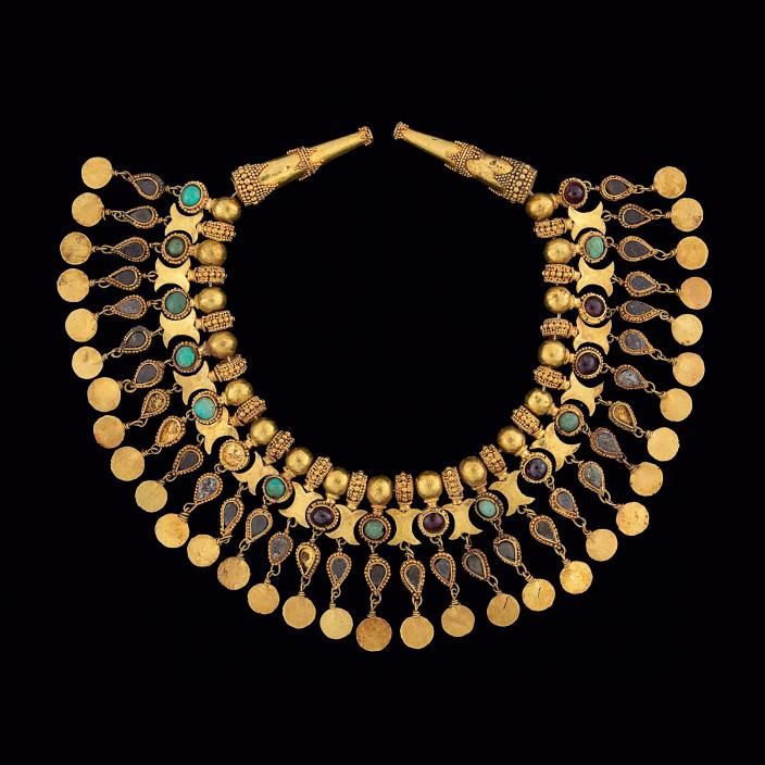 Ornament for the neck of a robe: Tillya Tepe, Tomb 5, Second Quarter of the 1st century CE, Gold, turquoise, garnet, pyrites. The other type of pendant consists of granulated rings with a spacer in the form of a double crescent attached. Both of these pendant types have further suspended decoration, first an almond shaped setting with a dark semi-precious stone, and below that a round gold disc.
