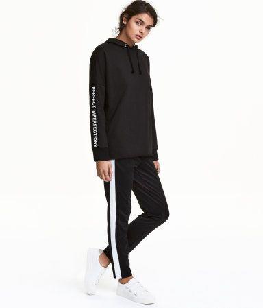 Schwarz/Weiß. Jogginghose aus Retromaterial mit seitlichen Kontraststreifen. Die Hose hat einen elastischen Bund und paspelierte Seitentaschen.
