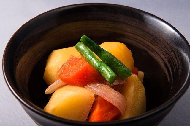 たっぷりの煮汁でじっくり煮る「ふくめ煮」 まずは「ふくめ煮」。これは薄めに味付けしたたっぷりの煮汁で、時間をかけて味を含ませるように弱火で煮る料理です。おいしく作る秘訣は、火を止めた後、冷ましながら味をしっかり含ませされるかどうか。煮上がったときに、鍋に汁気がほとんど残っていないのも特徴です。じゃがいも、里芋、かぼちゃなど、でんぷん質が多い根菜のほっくりした食感をいかすための煮方といえるでしょう。いかに煮崩れさせずに、材料の持ち味をいかして仕上げるかが鍵です。 短時間でさっと煮上げる「煮びたし」 薄めに味付けしたたっぷりの煮汁を使うという点では、野菜の「煮びたし」も同じ。ただし、こちらは中火で時間をかけず、さっと煮上げる煮物です。小松菜、ほうれんそう、白菜などの葉物やカブのように火が通りやすい野菜と、油揚げや桜えび、じゃこ、あさりなど、旨味とだしが出る素材を組み合わせて作る煮物が「煮びたし」です。ちなみに魚の「煮びたし」の場合は、焼いたり干したりした魚を薄味のたっぷりの煮汁でじっくり煮含めます。 ころころ転がすから「煮ころがし」…