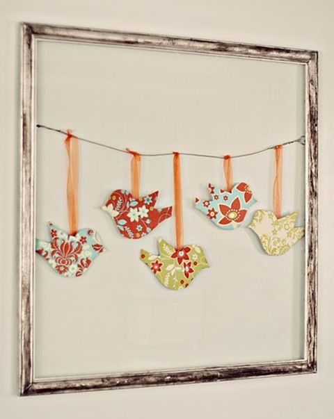 Birds on a Wire; simply mod podge fabric onto some birds bought at Michael's for a dollar and then hung them on a wire suspended in a thrift store frame. Love how the glass was left off the frame and combined the aged silver frame with the bright, patterned fabrics.