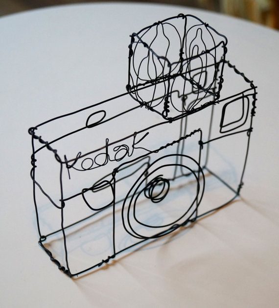 This unique sculpture is made from black galvanised wire and black florist wire, its a skeleton of an old Kodak camera with a box flash. Ideal