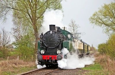 Steam train slowing down to cross a level crossing photo