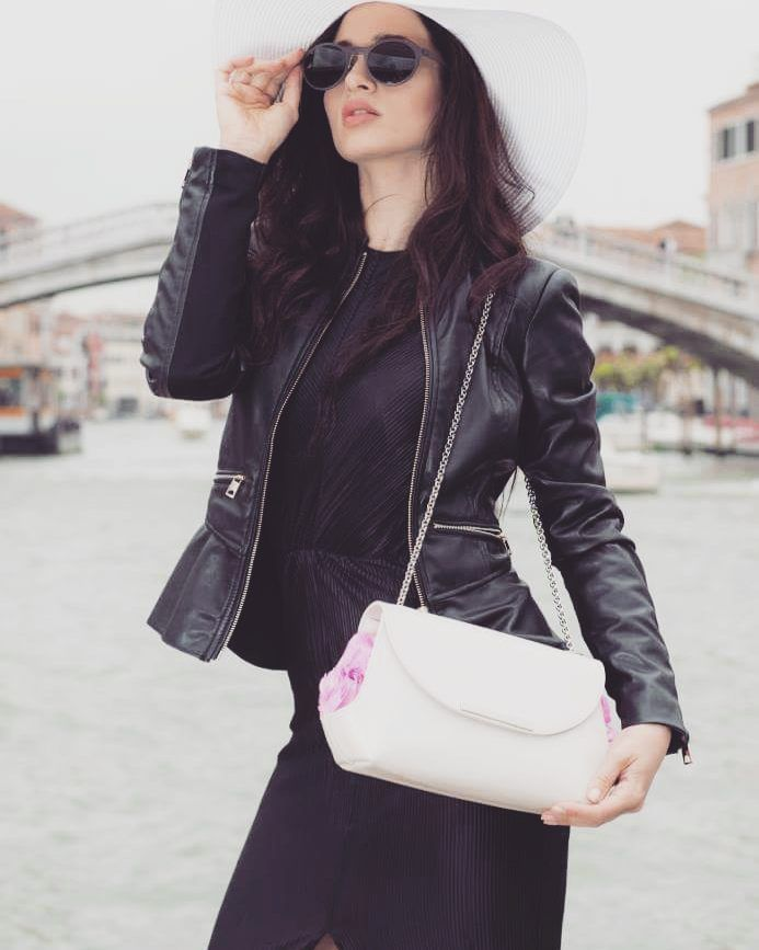 Venice Chic. Total black outfit #pencilskirt  #leatherjacket and a white leather #clutchbag with stabilized #pink #roses by #linfaglam. #chic #venice #blackoutfit #whitecap #posh #italy #photoshoot #handbags #bags #baglovers #clutch