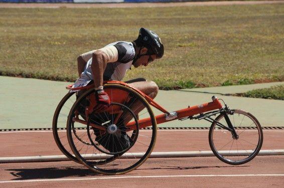 Um atleta, usando óculos escuros e capacete, movimenta uma cadeira de rodas numa…