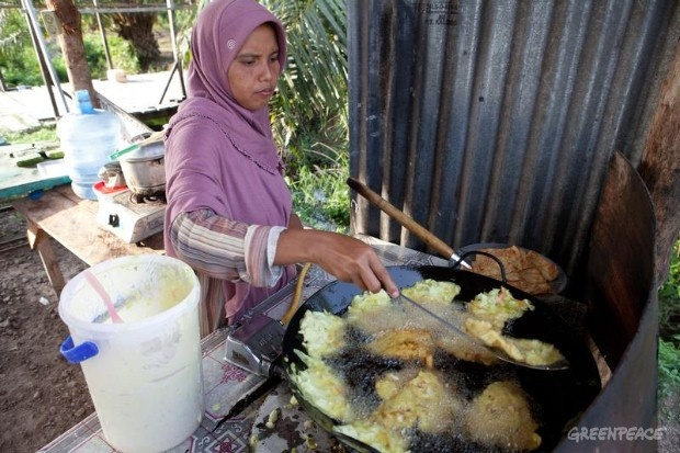 Frying food with palm oil in a street stall in Dosan village, Sumatra.