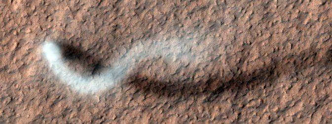 A towering dust devil, casts a serpentine shadow over the Martian surface in this image acquired by the High Resolution Imaging Science Experiment (HiRISE) camera on NASA's Mars Reconnaissance Orbiter. Image credit: NASA/JPL-Caltech/Univ. of Arizona