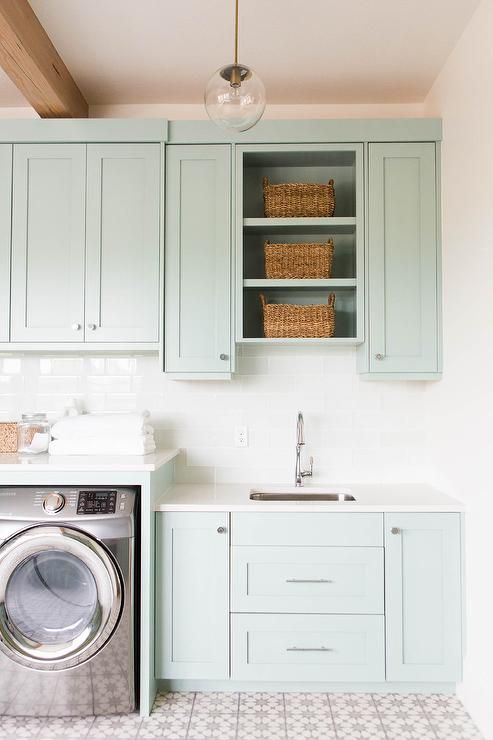 Beautiful laundry room with gray green cabinets paired with white quartz countertops and a white glass subway tiles backsplash.