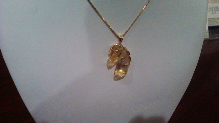 A horse's head shaped in quartz with an 18k yellow gold main adorned with three small diamonds and suspended on a 10k yellow gold chain.